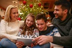 Familie die pret hebben terwijl het kijken samen Kerstmisfoto's stock foto