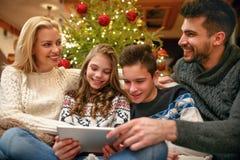 Familie die pret hebben terwijl het kijken samen Kerstmisfoto's royalty-vrije stock foto