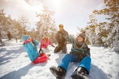 Familie die pret op sneeuw in berg hebben bij de winter stock afbeeldingen