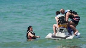 Familie die pret op straalski hebben bij strandeiland stock foto's