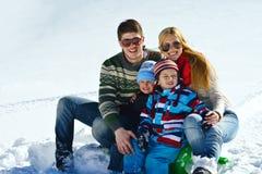 Familie die pret op verse sneeuw hebben bij de wintervakantie Stock Afbeeldingen