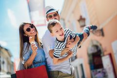 Familie die pret openlucht na het winkelen hebben stock afbeeldingen