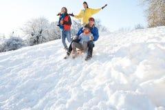 Familie die Pret Sledging onderaan SneeuwHeuvel heeft Royalty-vrije Stock Fotografie