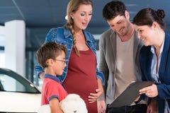 Familie die prijs van nieuwe auto bespreken met verkoopvrouw royalty-vrije stock afbeeldingen