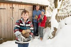 Familie, die Protokolle vom hölzernen Speicher im Schnee montiert Stockfoto