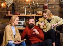 Familie, die reizenden Abend in der Landschaft verbringt Frauenlesebuch, während ihr Ehemann und Tochter Tee trinken stattlich lizenzfreie stockfotos