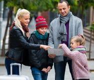 Familie, die Richtung in Karte überprüft Lizenzfreies Stockfoto