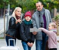 Familie, die Richtung in Karte überprüft Stockfoto