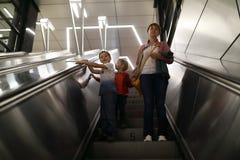 Familie, die Rolltreppe hinuntergeht stockfotografie
