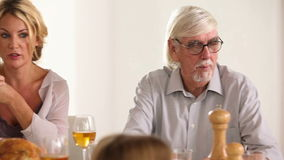 Familie die rond de lijst bij diner spreken stock videobeelden