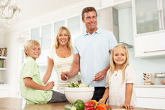 Familie, die Salat in der modernen Küche zubereitet Stockfotografie
