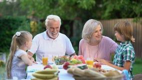 Familie die samen in openlucht en camera, zeker over toekomst bekijken dineren stock video
