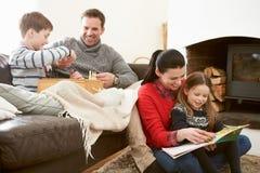 Familie, die Schach-sich entspannt und Lesebuch zuhause, spielend lizenzfreies stockbild