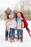 Familie, die Schlitten durch Snowy-Landschaft zieht Lizenzfreies Stockbild