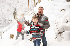 Familie, die Schneeball-Kampf in der Snowy-Landschaft hat Lizenzfreie Stockfotografie