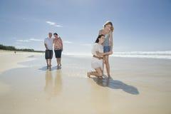 Familie, die Shell auf Strand betrachtet Stockbild