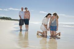 Familie die shell op strand bekijkt Royalty-vrije Stock Afbeeldingen