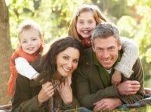 Familie, die sich draußen in der Herbst-Landschaft entspannt Lizenzfreie Stockfotos