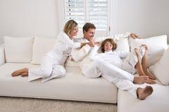 Familie, die sich zu Hause auf weißem Wohnzimmersofa entspannt lizenzfreie stockfotografie