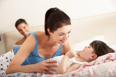 Familie, die sich zusammen im Bett entspannt Lizenzfreie Stockbilder