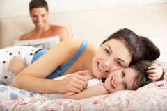 Familie, die sich zusammen im Bett entspannt Stockfotografie