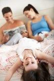 Familie, die sich zusammen im Bett entspannt Lizenzfreie Stockfotografie