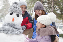 Familie die sneeuwman in een park in de winter maken Royalty-vrije Stock Foto's