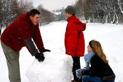 Familie die Sneeuwman maakt stock fotografie