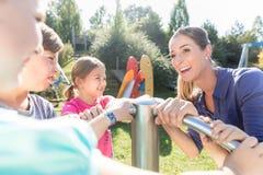 Familie, die Spaß am Abenteuerspielplatz im Park hat Stockbild