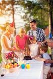 Familie, die Spaß beim Essen des Geburtstagskuchens hat stockfotografie