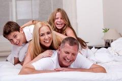 Familie, die Spaß im Bett hat Lizenzfreie Stockfotografie