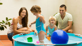 Familie, die Spaß im Kinderpool hat Stockfotografie