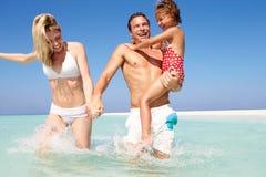 Familie, die Spaß im Meer am Strand-Feiertag hat Stockbilder