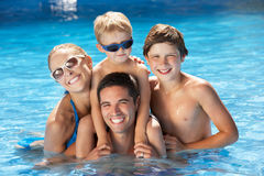 Familie, die Spaß im Swimmingpool hat Stockfotos