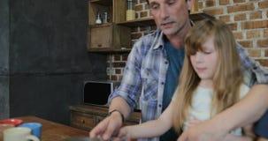 Familie, die spricht, beim Kochen in der Küche Kommunikation mit den Kindern erzieht, die zu Hause Lebensmittel für Abendessen zu stock footage
