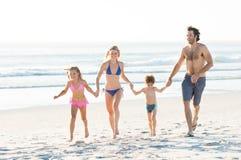 Familie, die am Strand läuft Lizenzfreies Stockfoto