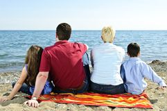Familie, die am Strand sitzt Stockbilder
