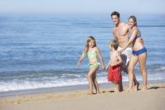 Familie die Strand van Vakantie genieten die langs Strand lopen Royalty-vrije Stock Afbeeldingen