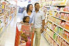 Familie die in supermarkt winkelt stock foto
