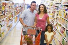 Familie die in supermarkt winkelt stock afbeelding