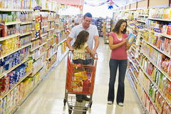 Familie die in supermarkt winkelt Stock Foto's