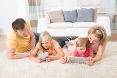 Familie die tabletten gebruiken die op tapijt liggen Stock Fotografie