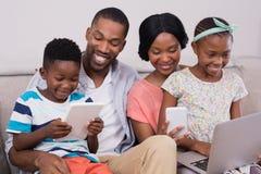 Familie die technologieën gebruiken terwijl thuis het zitten op bank royalty-vrije stock foto's