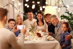 Familie, die Teeparty hat und zu Hause fotografiert stockbilder
