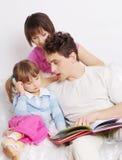 Familie die thuis boek leest Stock Foto's