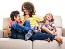 Familie die thuis de jongen van het moedermeisje bestrijden Royalty-vrije Stock Afbeeldingen