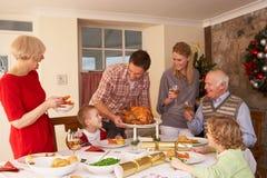 Familie die thuis diner dient bij Kerstmis Stock Foto's