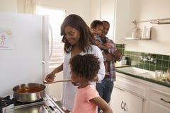 Familie die thuis Maaltijd in Keuken samen voorbereiden royalty-vrije stock afbeeldingen