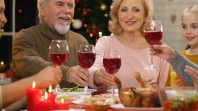 Familie die toost opheffen bij Kerstmisdiner, traditie om voor vakantie bijeen te komen stock footage