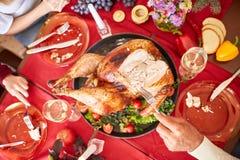 Familie die traditionele Dankzegging Turkije op een feestelijke lijstachtergrond eten Geroosterd Turkije Het concept van de famil Stock Afbeelding